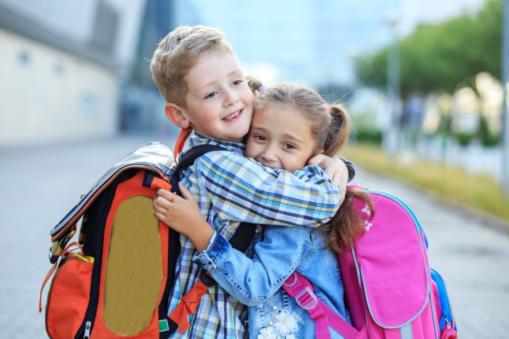back-to-school-boy-girl-met-backpacks-hugs-outdoor-education-happy-pupil-children-sister-brother_t20_jROk8r